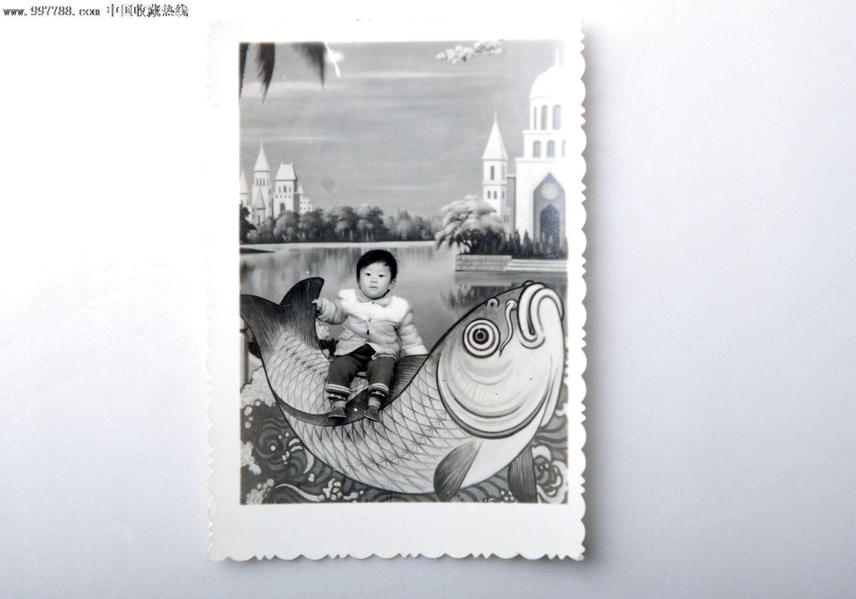 小孩骑鱼道具照片